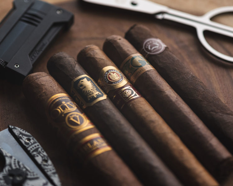 Lineup of gorgeous cigars with cutter in background