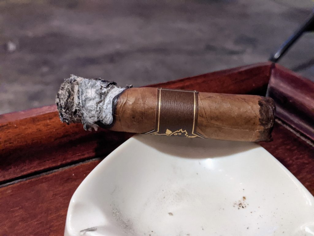 Room101 cigar with some ash hanging on.